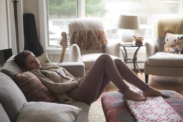 Teenage girl (14-15) relaxing on sofa