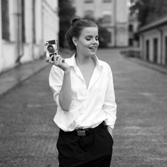 Girl photographer with retro film 35mm camera on street. Black and white