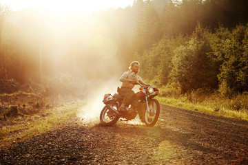 Young man sliding motorcycle on dirt road