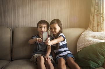 Siblings using mobile phone in living room