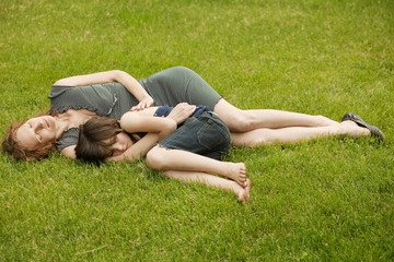 Mother and daughter (8-9) sleeping on grass in backyard