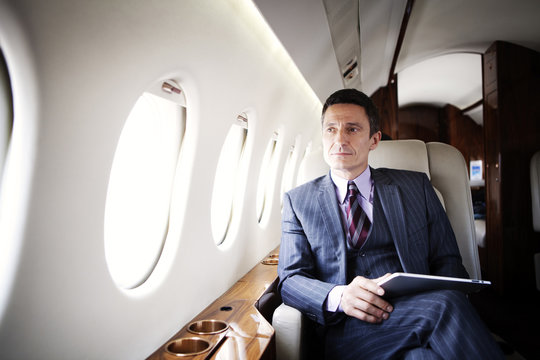 Man with tablet on airplane