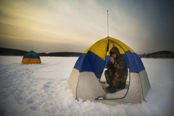 Senior man sitting inside tent in snowy plain