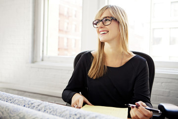 Woman smiling while writing at desk