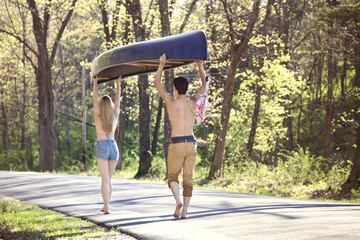Couple walking on road in forest and carrying kayak