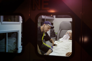 Emergency medical technician checking blood pressure of man in ambulance