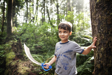 Boy (4-5) with cutlass in forest