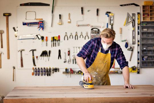 Carpenter sanding wood with sander in workshop