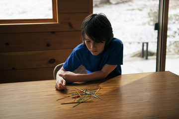 Boy (10-11) playing pick up sticks