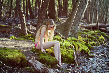 Teenage girl (16-17) sitting on rock in forest