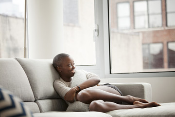 Young bald woman sitting on sofa in living room