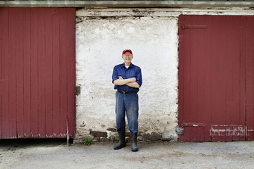 Portrait of farmer by barn doors