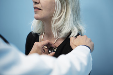 Doctor holding stethoscope to patient's chest