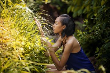 Young woman examining grass in backyard