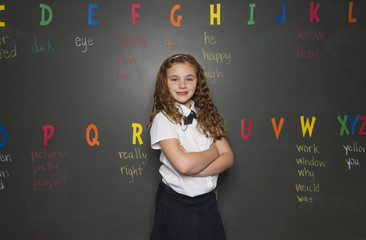 Smiling school girl (8-9) with arms crossed, standing in front of blackboard
