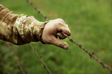 Mid adult man holding barbed wire