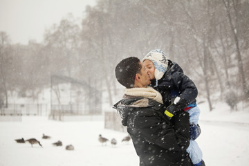 Father and son (4-5) outdoors in snow kissing