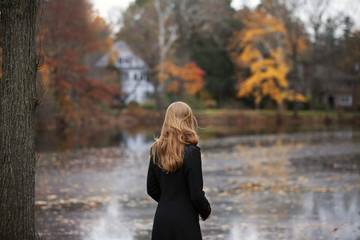 Young woman standing by river in autumn