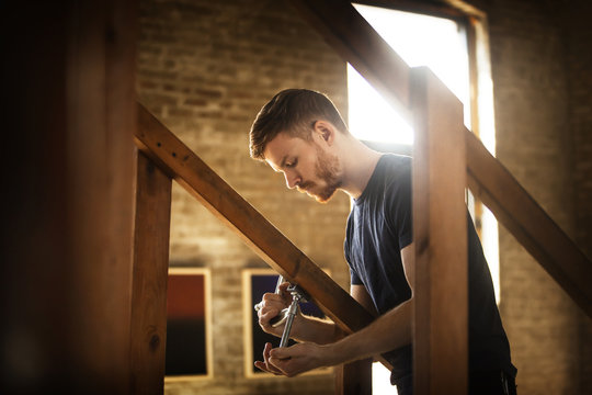 Young man repairing staircase