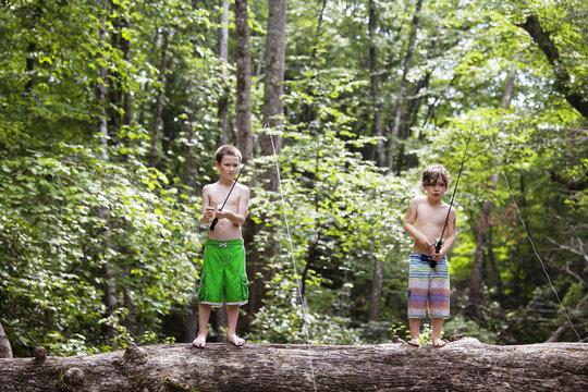Two boys (6-7, 10-11) fishing from fallen tree