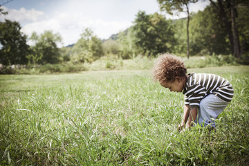 Girl (2-3) looking at grass in field