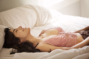 Smiling young woman on bed in lingerie