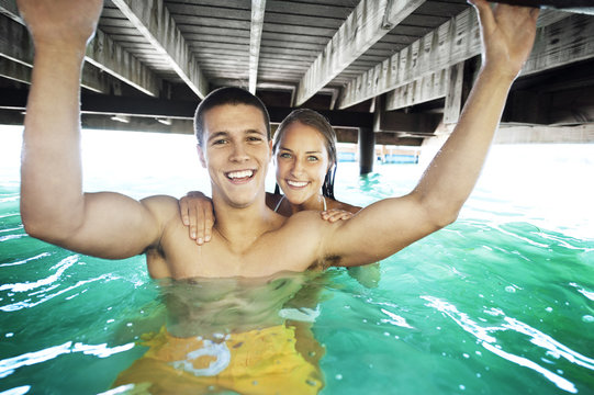 Couple swimming under pier at lake