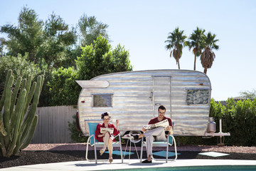 Couple reading newspapers in front of trailer home