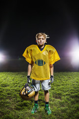 Portrait of American football player standing in field