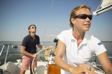 Man and woman controlling yacht against sky
