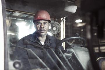 Portrait of mature steel worker in forklift