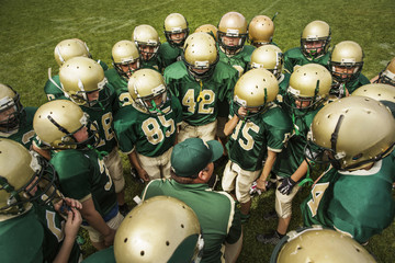 American football team discussing in football field