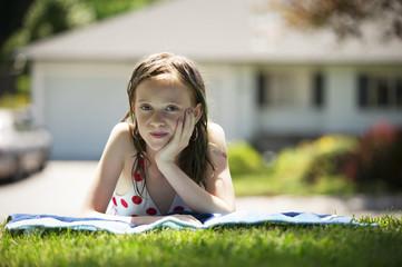 Girl (10-11) in bikini sunbathing on lawn