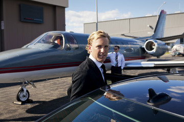 Portrait of businessman standing by car against airplane