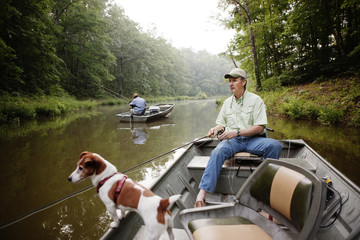 Men with dog fly fishing on river