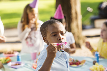 Boy blowing bubbles while friends in background at birthday party