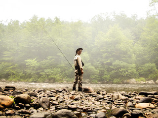 Fisherman standing on edge of stream