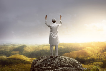Young muslim man praying on the mountain