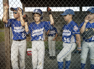 Portrait of boy with friends standing by fence in dugout