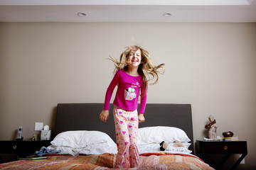 Girl (6-7) jumping on bed