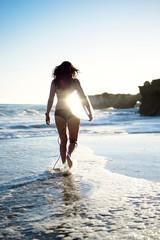 Rear view of surfer woman walking towards sea