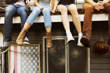 Low-section of teenage girl (16-17) sitting with friends on roof