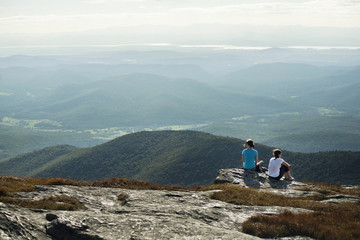 Two women sitting on mountain edge
