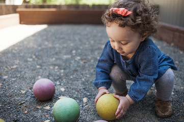 Baby girl (12-17 months) playing with balls