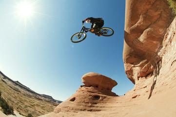 Mountain biker jumping on rock