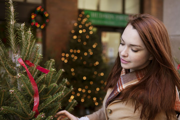 Young woman looking at christmas tree