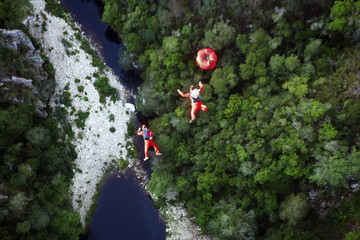 Two men base jumping in Santa Claus Costumes