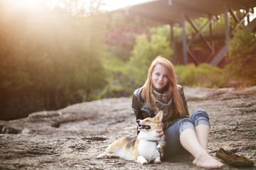 Young woman sitting with dog on rocks