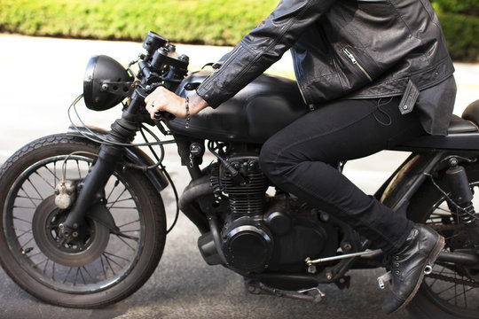 Cropped image of man sitting on motorcycle at road