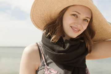 Portrait of woman wearing hat at beach